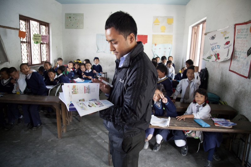 Photo of a young man as a school teacher in a classroom of little Nepalese children. He is thumbing through a picture book.