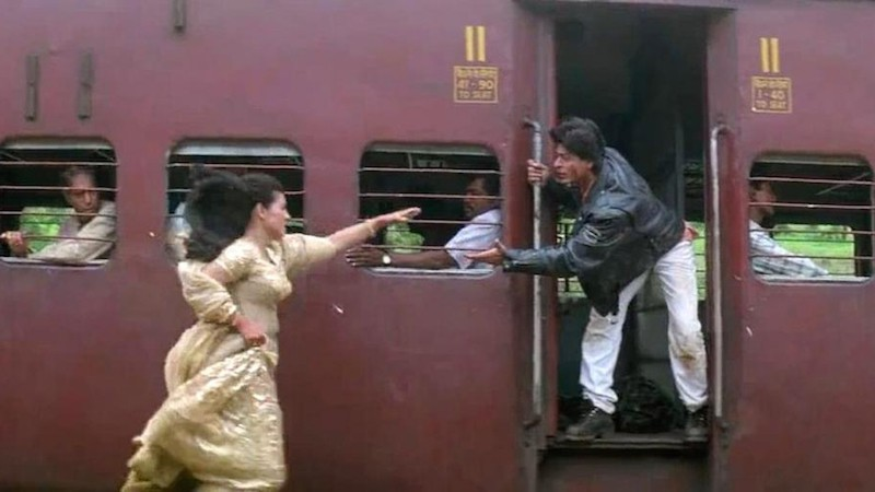 Still from DDLJ, Kajol running towards a running train while Shah Rukh Khan extenda a hand from the train