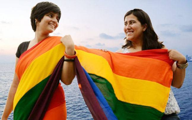 Two women stand side by side, one of them wears rainbow-coloured saree, and the one beside her drapes the pallu on her body