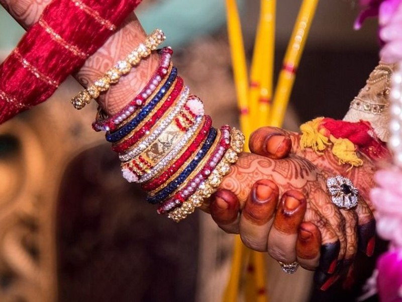 A zoomed in photograph of a couple holding hands during the marriage ceremony taking place. Both of them are wearing henna on their hands. The girl is wearing a set of bangles.