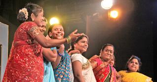 A photograph of a group pf women wearing sarees and speaking on the stage.