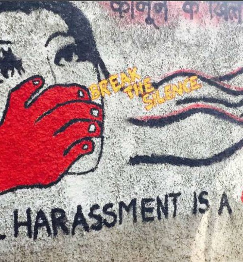 The photo shows a red hand trying to shut the mouth of a woman. There's a caption on the photo saying sexual harassment is a crime and a yellow caption in between says, break the silence.