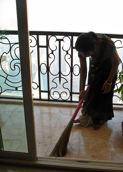 A photograph of a woman wearing a green saree cleaning the balcony with a broom.