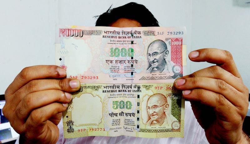 A photo of a man holding the old Rs.1000 and Rs.500 notes,