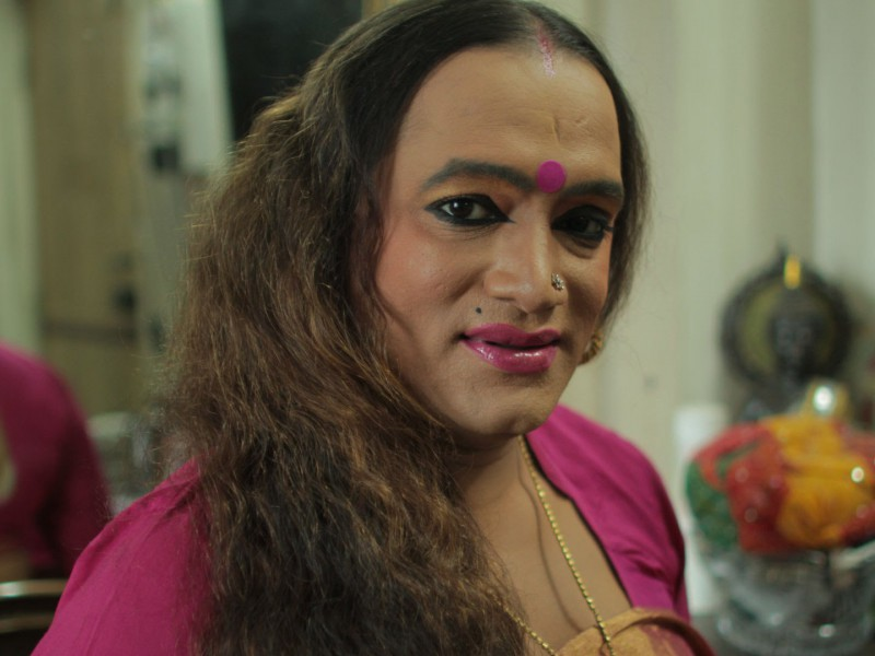 It's a still from the video, Laxmi, is smiling and wearing a pink bindi and saree, a silver nose pin. They have long hair, open in the photo and is wearing sindoor on their forehead.