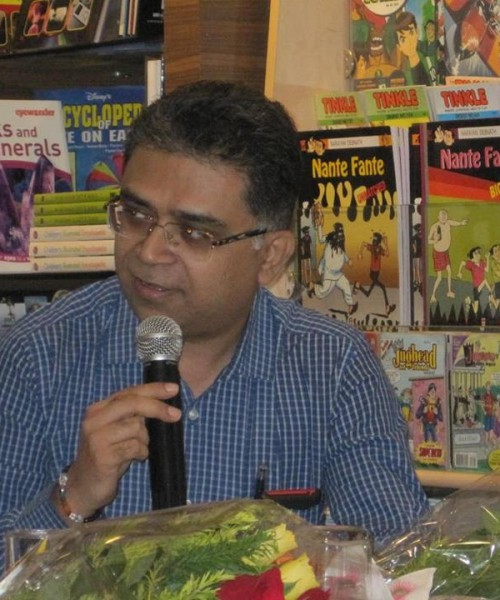 A photo of Pawan Dhall wearing a blue shirt, speaking on the mike with book shelves in the background