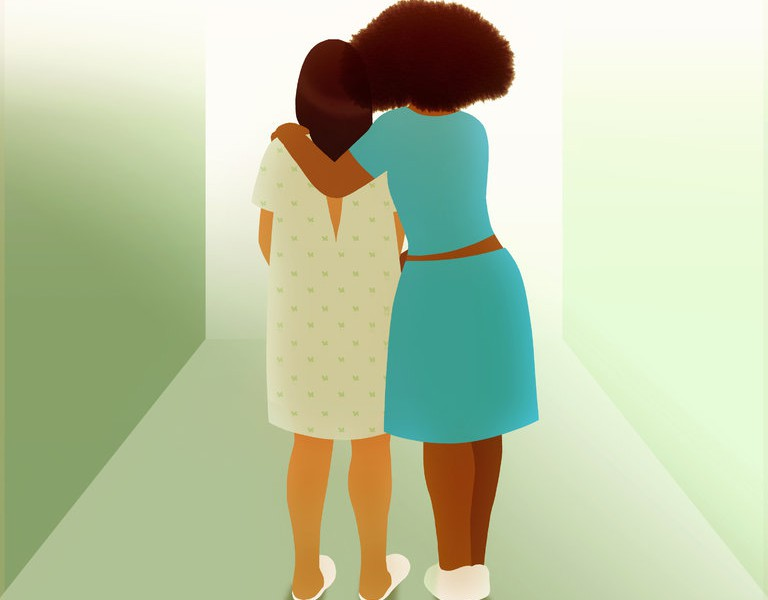 Two women standing facing their backs,side-hugging eachother. One is wearing a hospital gown, has long hair. The other woman has brown curly hair, is wearing a blue dress.