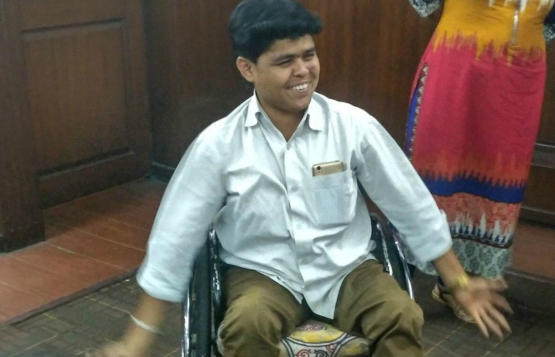 Kiran sitting on a wheelchair, smiling. He is wearing brown pants and a white shirt, and has his cellphone peeking out of his top shirt pocket.