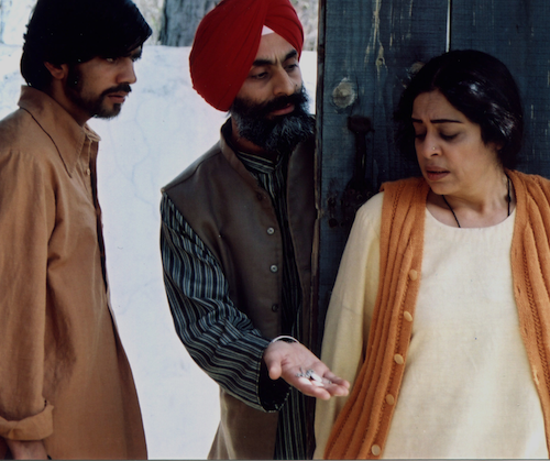 Its a still from the movie, Khamosh Pani,featuring Kirron Kher, standing with her back towards two men, one is a Sikh wearing a red turban offering something to the woman and the other man is looking towards them. Screen reader support enabled. Its a still from the movie, Khamosh Pani,featuring Kirron Kher, standing with her back towards two men, one is a Sikh wearing a red turban offering something to the woman and the other man is looking towards them.
