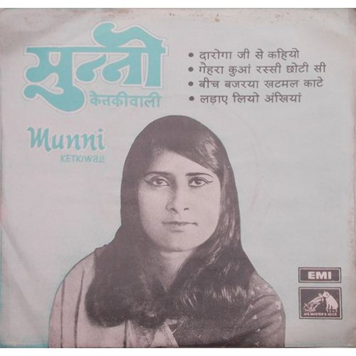 Its a poster of the singer, Munni Ketki Wali. Its in black and white, where a lady is smiling, wearing winged eye-liner, she has long hair. The caption on the poster says, मुन्नी केतकीवाली, Munni Kethkiwali and the names of her songs- दरोगा जी से कहिये गहरा कुआँ रस्सी छोटी सी बीच बज्रया खटमल काटे लढाये लियो अँखियाँ