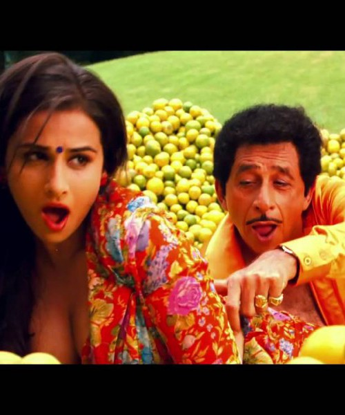 Still from a Hindi film 'The Dirty Picture' (2011). A brown woman has open black hair, is wearing a black bindi, and a bright-coloured, deep-neck blouse. A man behind her is touching her waist. There are piles of oranges in the garden around them. They both are singing a song.