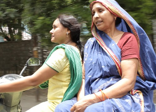 Two women riding a scooter. A younger Indian woman wearing a low pony-tail and a suit is on the wheel, with an older woman who is wearing a saree with which she covers her head, is sitting at the back facing sideways.