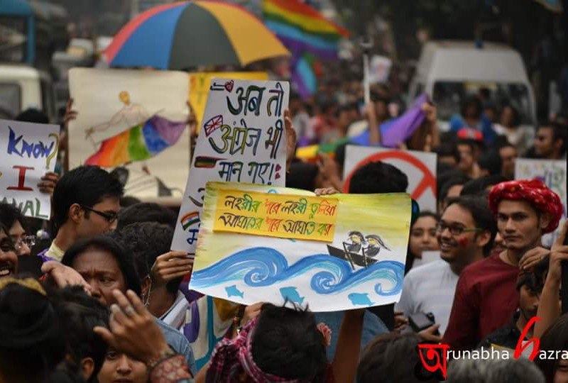"""Photo of a vibrant queer pride march. There is a huge crowd, lots of rainbow-coloured umbrellas, flags, drawings, and writings on placards. One placard reads """"ab toh angrej bhi maan gaye"""" in Hindi."""