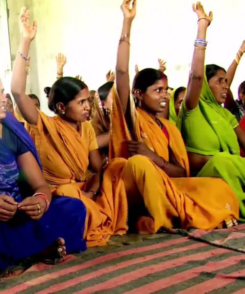 Several young Indian rural women sitting in a row on a carpet. Some have raised their hands, as if in answer to a question. They are wearing bright-coloured sarees, and bangles. Some are wearing bindis too.
