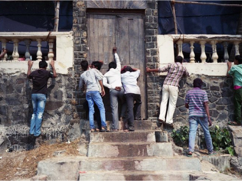 A few men knocking the door of an old Indian house. A few other men are trying to peek into the house through a very low railing.