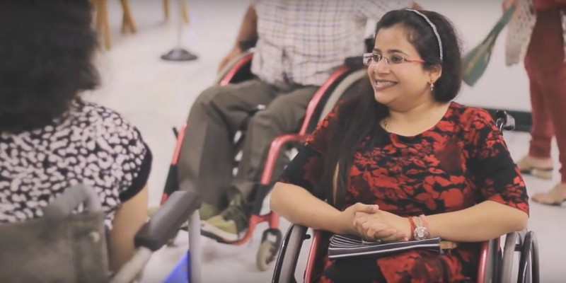 A woman in a wheelchair, smiling, conversing with another woman who is also on a wheelchair. She has long hair pulled to one side, is wearing frameless specks, and is wearing a red and black top.