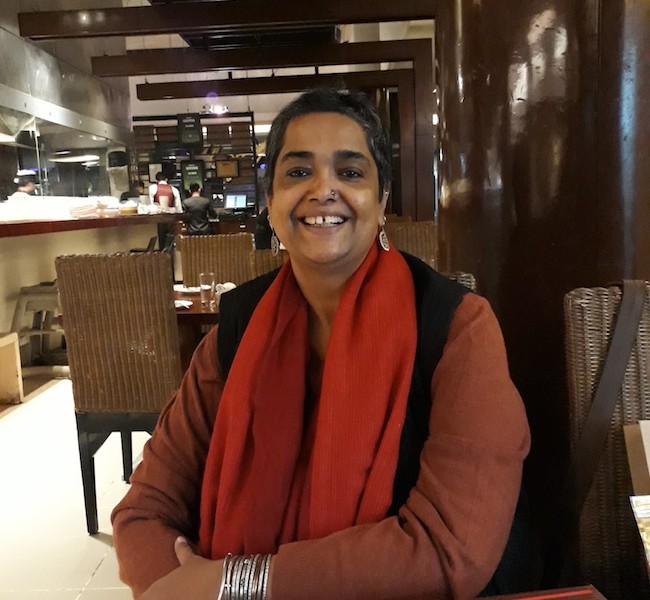Picture of feminist activist Pramada Menon, she ihas short hair and is wearing a maroon kurta, black waistcoat and a red dupatta