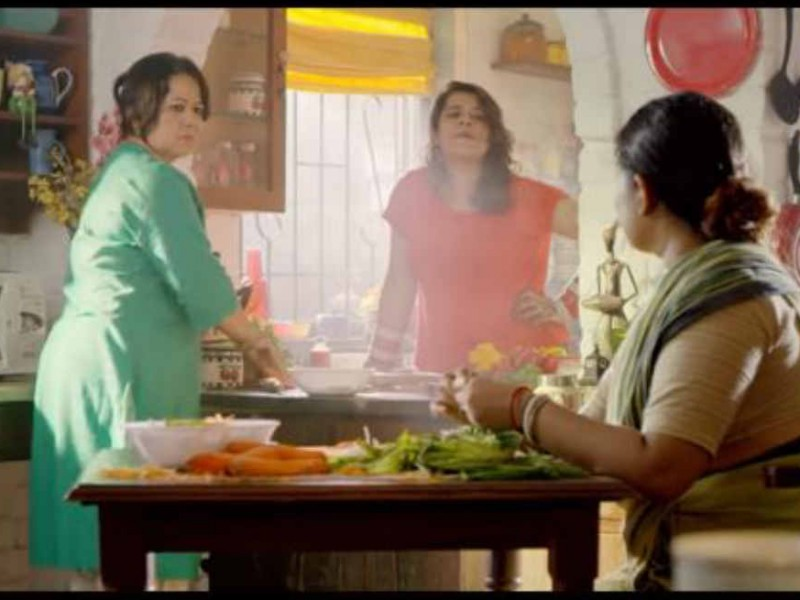 A still from a video. A mother, a daughter, and a maid are coversing while working in the kitchen.