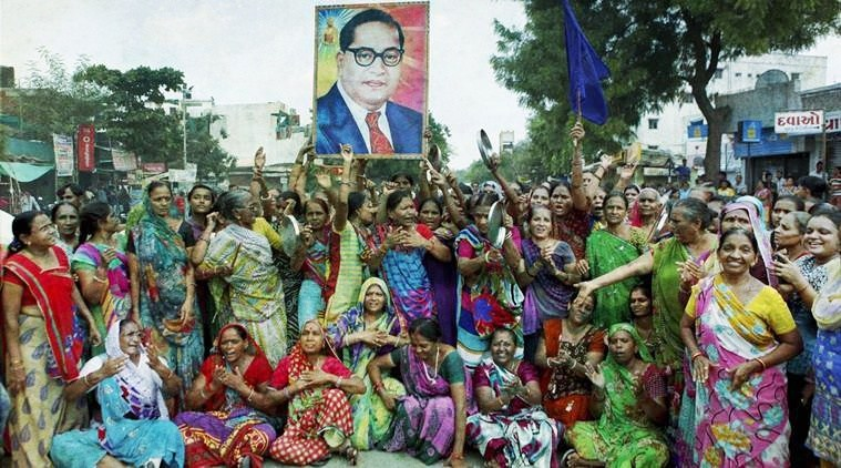 Women members of the Dalit community carry a portrait of B.R. Ambedkar as they block the traffic during a protest in Ahmedabad against the assault on Dalit members by cow protectors in Rajkot district, Gujarat. Credit: PTI