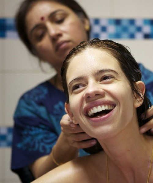 """Still from an Hindi film """"Margarita with a Straw"""". A young woman with oily hair is laughing. An older woman wearing a blue nightgown is massaging her hair."""
