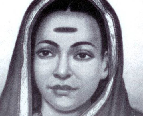A black-and-white headshot of Savitribai Phule. She has covered her head with her saree, which has a white border. She is looking straight, expression-less. She has a big horizontal mark right at the centre of her forehead.
