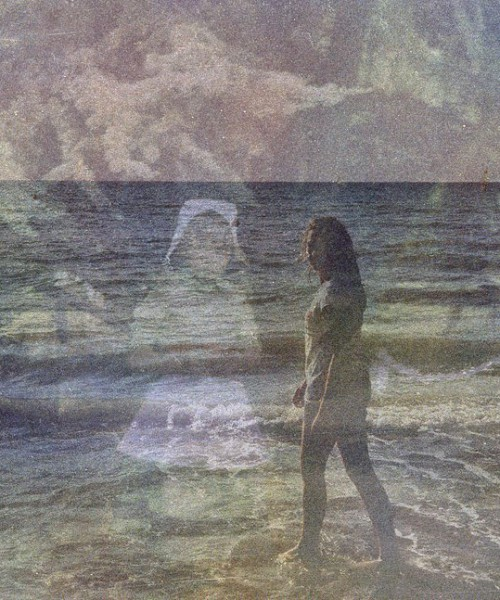 Two pictures are superimposed on each other. In the foreground is a picture of a woman standing on a beach. In the background is a picture of a little girl staring straight at us.