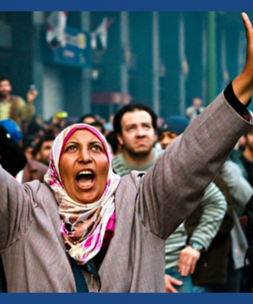 On a foggy winter morning, a woman protestor waves a victory sign, looks upwards, and shouts what could be possibly be a slogan. She wears a pink and white coloured headscarf and a grey coat. There are hoards of other protestors in the background too.