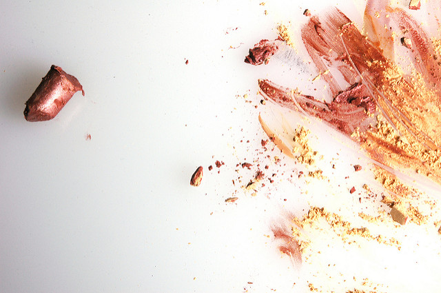 A broken piece of copper-shaded lipstick on the right, with lipstick marks of copper and yellow lisptick smudged on the left.