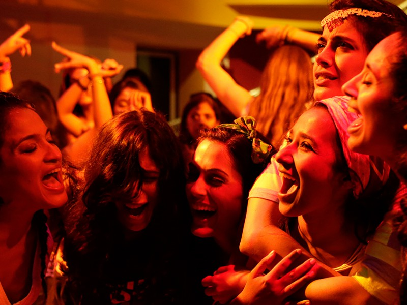 Scene from a Hindi movie 'Angry Indian Goddesses'. The six protagonists are standing together laughing, in a disco with bright lighting.