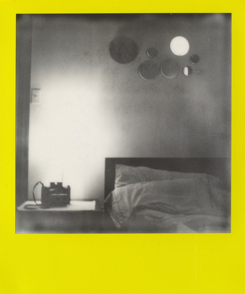 A black-and-white picture of a room, with a mussed bed and a bedside table.