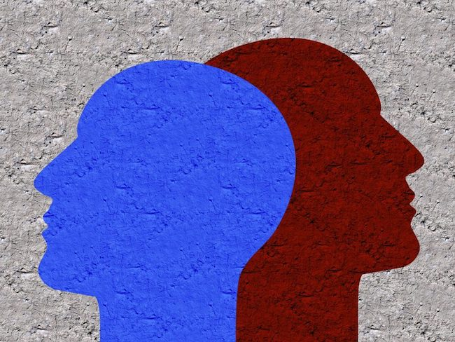 A blue and a red silhouette of the heads of two figures leaning against each other.