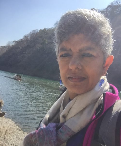 Photo of activist Nandini Rao. She has white hair and is wearing a jacket and scarf.