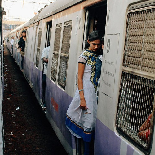 Photo of a woman standing in the entrance of a local train in Mumbai