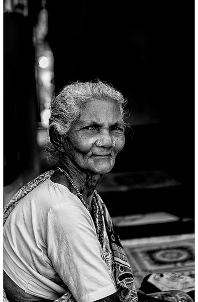 A black-and-white picture of an old woman who is staring directly into the camera.