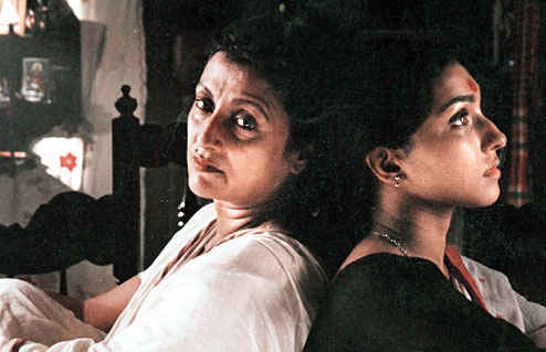 A still from 'Paromitar Ek Din', showing actors Rituparna Chatterjee and Aparna Sen leaning against each other.