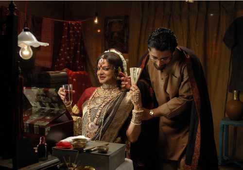 Still from the film: Arekti Premer Golpo, showing a man crossdressed as a woman, wearing a cotton sareer, red blouse, and gold jewellery