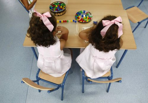 An image of two little girls sitting at a table, facing their backs to the camera. Marcelo del Pozo / Reuters