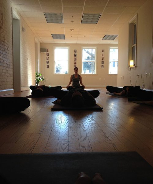 picture of a woman meditating in an empty room with dark brown interiors