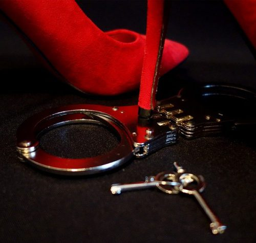a picture of bdsm handcuffs lying on the floor with someone's foot wearing a heel beside it