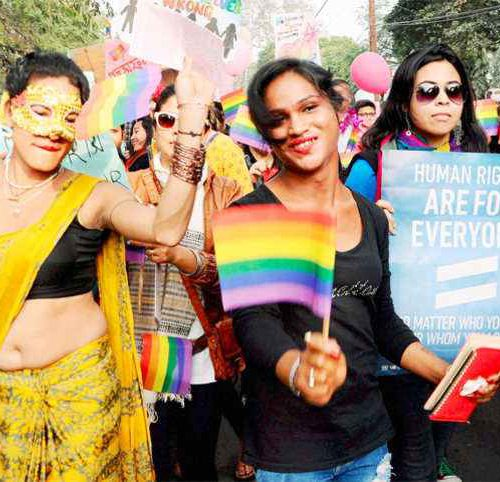 A picture from a pride parade; in the center, a woman in a black shirt holds up a pride flag, to her right, a trans woman in a bright orange saree wears a golden mask, and to her left, a woman in a green top holds up a placard with a slogan