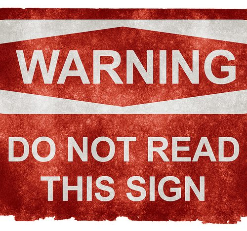 """against a red background, the white text reads """"warning, do not read this sign"""""""