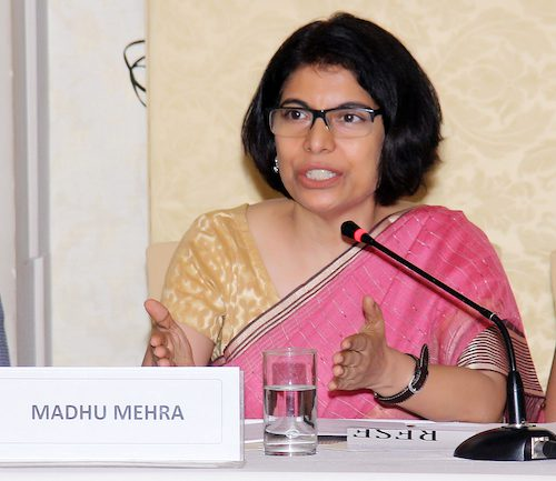 picture of lawyer and activist madhu mehra. she wears a pink saree with a beige blouse and sits at a desk before a microphone