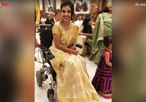 Picture of a woman in a wheelchair. Her hair is tied back in a bun and she is wearing a white saree and makeup.