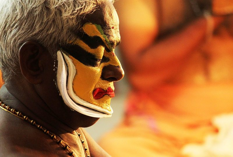 Picture of a classical dance performer, face painted in yellow and black