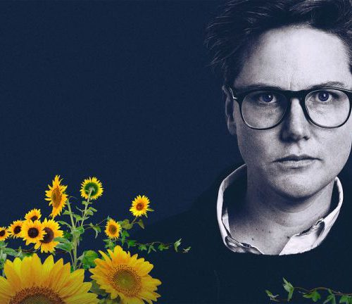 Black and white picture of stand-up comic Hannah Gadsby. She has short hair and wears dark glasses.