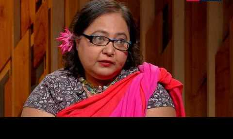 Picture of Paromita Vohra, she has short hair, wearing a pink saree and black blouse with a flower in her hair