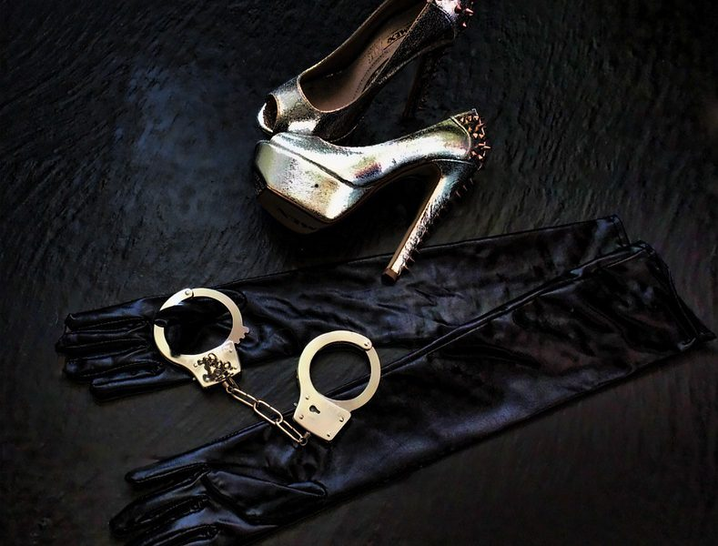 Picture of a pair of heels and a steel handcuffs , along with black silk gloves lying on the floor