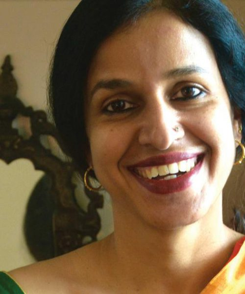 Picture of author Madhavi Menon. She is wearing a yellow saree.
