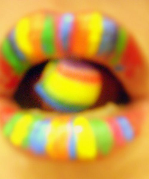 Picture of a woman's mouth, with her lips and tongue painted in rainbow colours