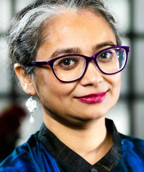 Picture of author Manjima Bhattacharya. She has short white-and-grey hair and is wearing dark thick-rimmed glasses